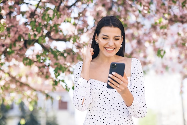 여자는 휴대 전화에서 성공을 즐긴다 즐거운 소녀는 승리를 축하하는 전화로 좋은 소식을 읽고