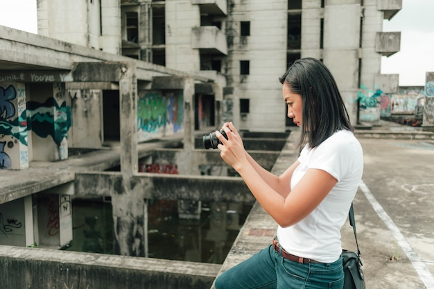 Woman enjoy taking photo of an unknown abandoned building.