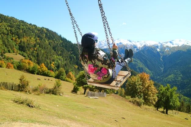 Женщина наслаждается качелями с удивительным панорамным видом на горы кавказа в городе местия, грузия