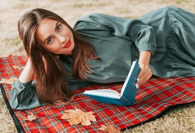 피크닉 담요에 책을 즐기는 여자