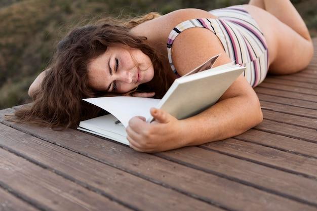 Женщина наслаждаясь книгой outdoors