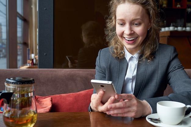 電話で良いメッセージを楽しんでいる女性。感情、驚き、喜び