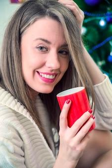 リビングルームのソファでリラックスして、新鮮な紅茶の大きなカップを楽しんでいる女性。朝のコーヒー。女性、赤、コーヒー、カップ