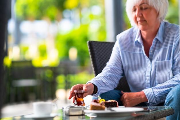 パティオでお茶とケーキを楽しむ女性