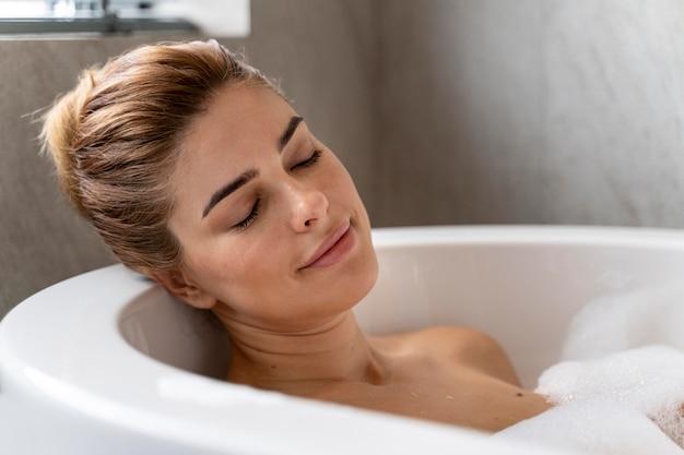 リラックスできる泡風呂を楽しむ女性