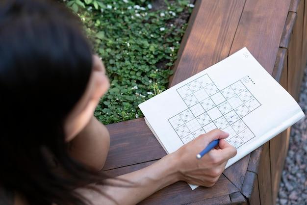 혼자서 종이 위에서 스도쿠 게임을 즐기는 여성