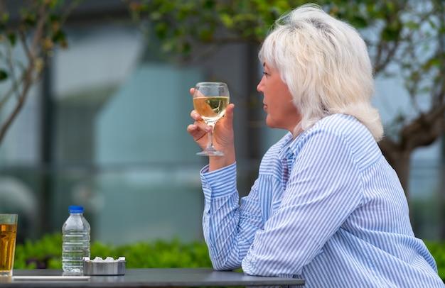レストランのテーブルで白ワインの食前酒を楽しむ女性