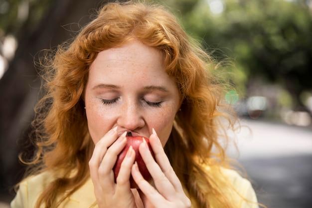 Woman enjoying an apple outdoors