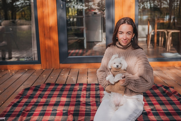 Woman enjoying in autumn day with white puppy outdoors