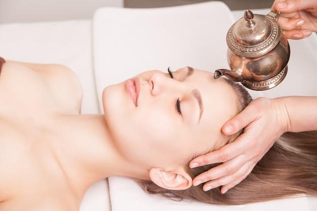 Woman enjoying a ayurveda oil head massage treatment in spa