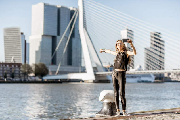 Woman enjoying beautiful cityscape view on the modern riverside during the morning in rotterdam city