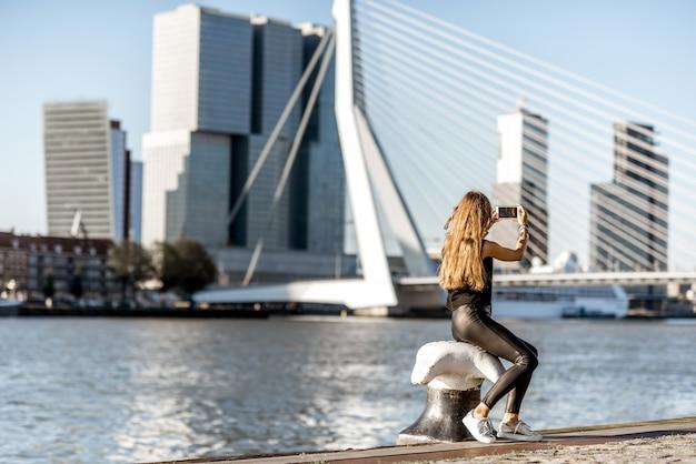 ロッテルダム市の朝の間にモダンな川沿いの美しい街並みの景色を楽しむ女性