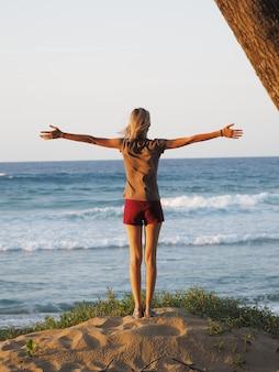 올려진 손으로 서 있는 바다의 아름다운 전망을 즐기는 여자.