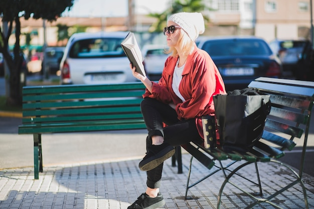 Woman enjoying book on street