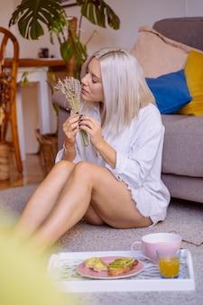 Женщина наслаждается завтраком и пахнет ароматными травами