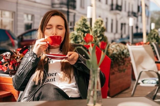 赤いカップのストリートカフェのテーブルでコーヒーを楽しむ女性