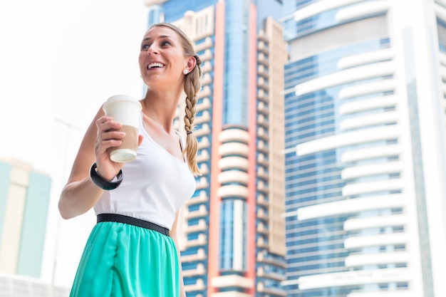 Woman enjoying coffee to go in metropolitan city