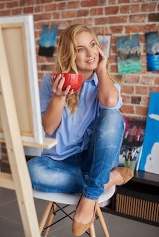 アートスタジオでコーヒーを楽しむ女性