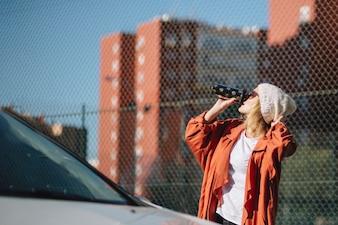 Woman enjoying coffee near car