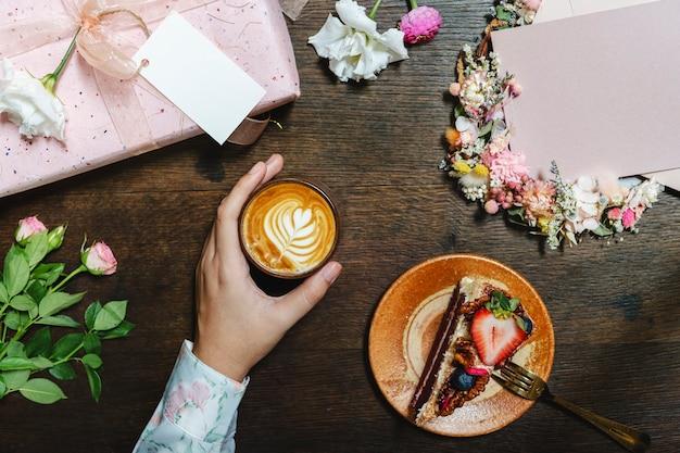 딸기 케이크 한 조각과 함께 커피를 즐기는 여자