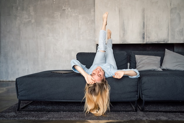 Woman enjoying on a couch with head upside down.