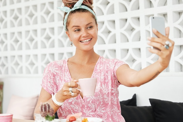 Женщина, наслаждающаяся десертом и напитком в кафе