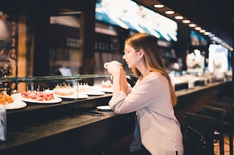 Woman enjoying drink at cafe counter