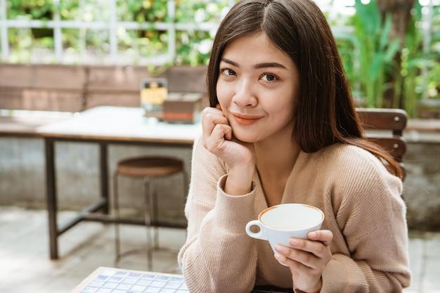 Женщина наслаждается пить кофе в кафе