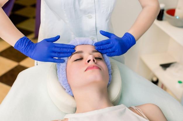 Woman enjoying face massage in beauty center