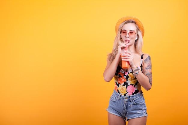 黄色の背景にサングラスと帽子と新鮮なオレンジジュースを楽しんでいる女性