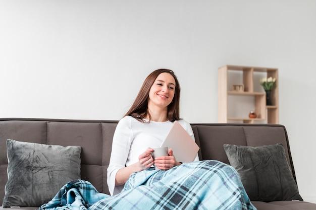 Женщина, наслаждаясь ее время дома на диване