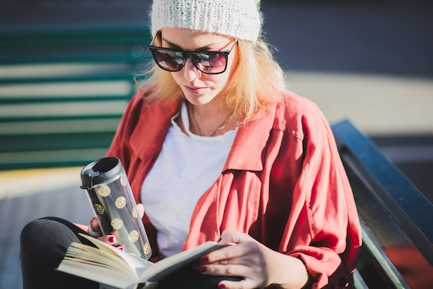 Woman enjoying hot drink and book
