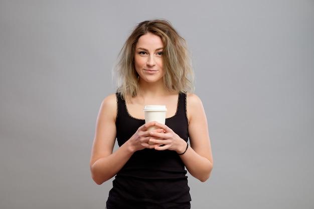 使い捨て紙コップで温かい飲み物を楽しんでいる女性