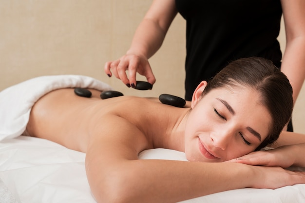 Woman enjoying hot rocks therapy at spa