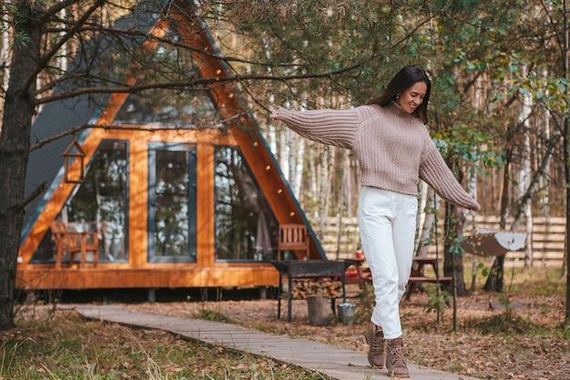 彼女の家の秋の日に楽しんでいる女性