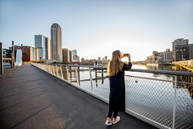 ロッテルダム市の朝の間に橋の上に立ってモダンな街並みの景色を楽しむ女性