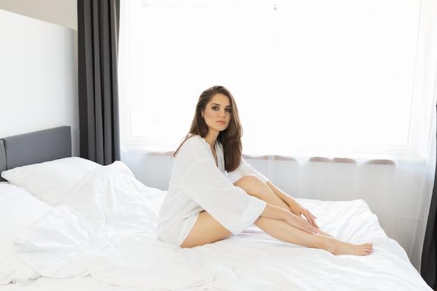 Woman enjoying morning awakening in a soft snow white bed.