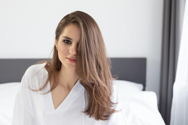 Woman enjoying morning awakening in a soft snow-white bed.