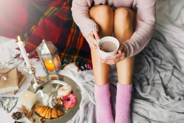 彼女のベッドで朝の時間を楽しんでいる女性、暖かい居心地の良いウールのセーターとピンクの靴下を着て、大きなコーヒーのカップを保持しています。