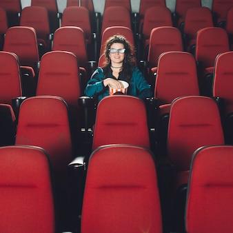 Женщина, наслаждаясь фильмом в пустой аудитории