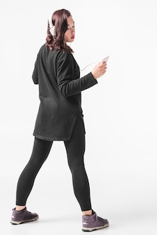 Woman enjoying music on headphone against white backdrop
