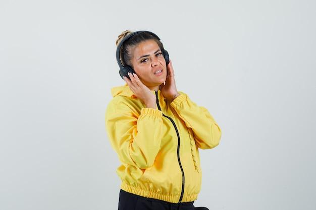 スポーツスーツを着てヘッドフォンで音楽を楽しんでいて、かわいく見える女性、正面図。