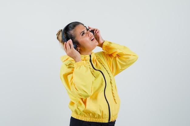Женщина, наслаждающаяся музыкой в наушниках в спортивном костюме и мечтательная. передний план.
