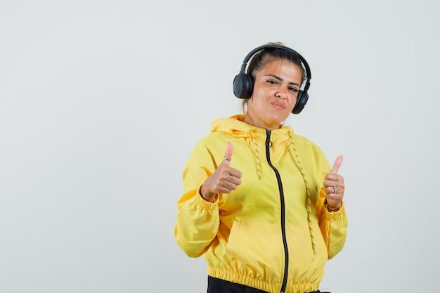 헤드폰으로 음악을 즐기는 여자, 스포츠 정장 전면보기에 엄지 손가락 uo를 보여주는.