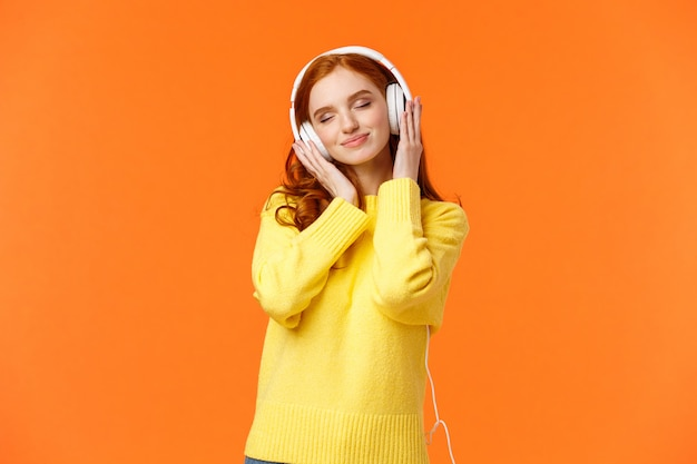 Woman enjoying nice soft sound of headphones. cheerful romantic and delighted pretty redhead woman