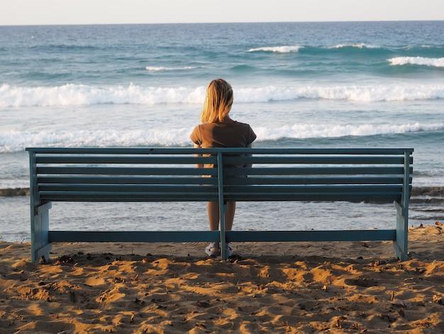 일몰에 벤치에서 바다 전망을 즐기는 여자. 뒷모습.