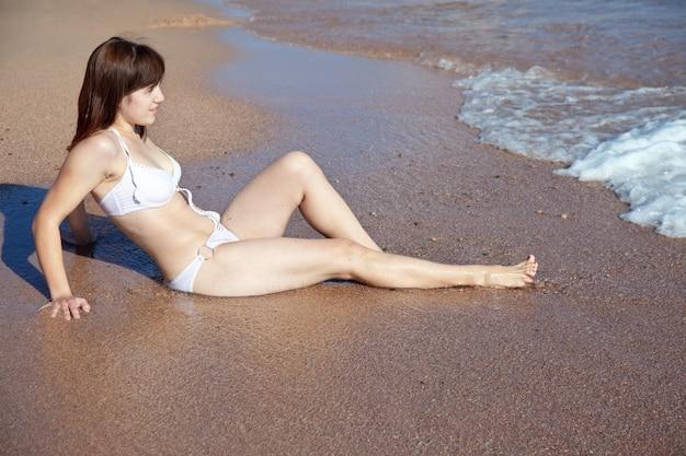 Женщина, наслаждаясь на песчаном пляже