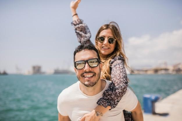Woman enjoying piggyback ride on his boyfriend's back