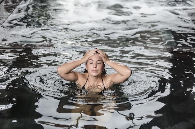 Женщина, наслаждающаяся бассейном в спа-центре