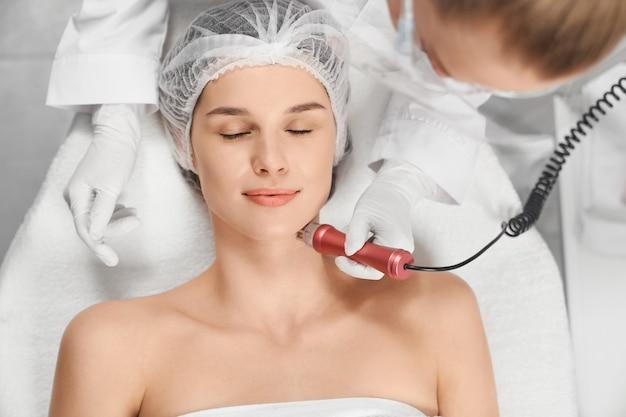 Donna che gode della procedura di pulizia o massaggio per il viso